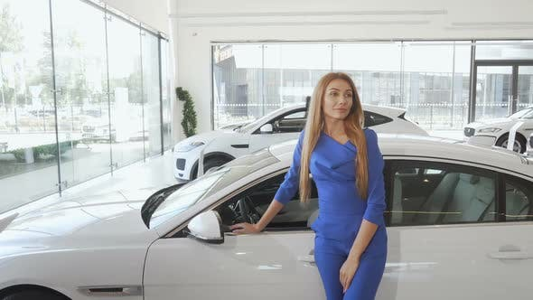 Cover Image for Attractive Elegant Woman Looking Away Dreamily Standing Near New Car