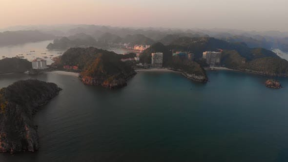 Thumbnail for Aerial: sunset clear sky at Cat Ba island and beach with new tourist resort, Halong bay Vietnam