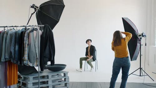 Slow Motion of Female Photographer Taking Pictures of Male Model in Studio