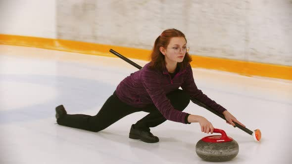 Thumbnail for Curling - a Young Woman in Glasses Pushes Off in the Ice Field with a Granite Stone