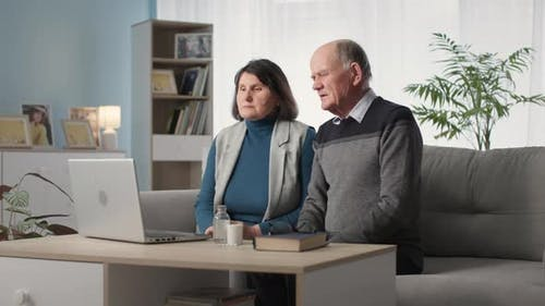 Married Couple Feeling Unwell Communicates with Doctor Online Via Video Call on Laptop While Sitting