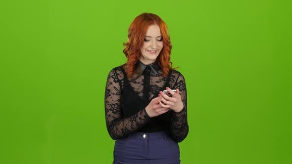 Thumbnail for Girl Looks Into the Phone, Selects the Information She Needs. Green Screen