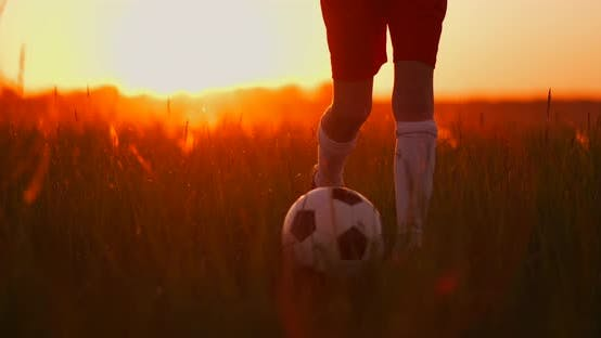 Cover Image for Tracking a Boy Football Player Running with a Ball on Camera at Sunset
