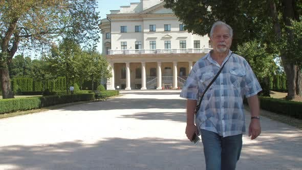 Thumbnail for Grey Haired Old Man Walks Along Green Park Zone Against Sky