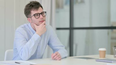 Young Man Sitting in Office Thinking