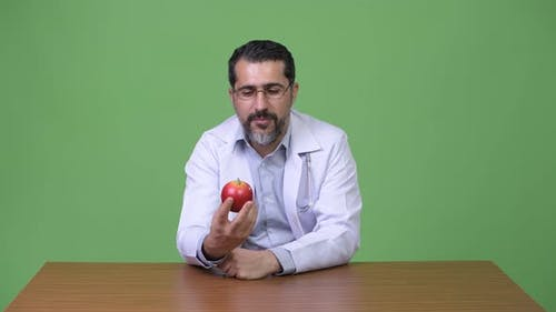 Handsome Persian Bearded Man Doctor Talking While Holding Apple