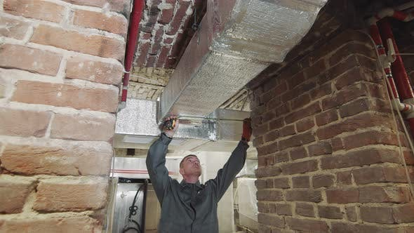The Master Carries Out Measurements of Ventilating Channels on Construction. The Employee Measures