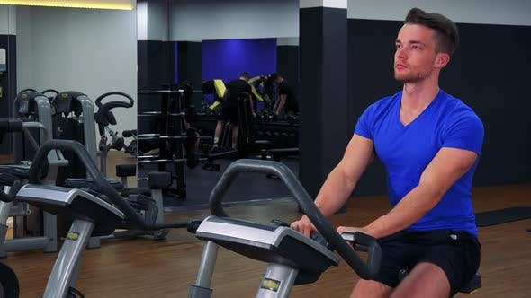 Thumbnail for A Young Fit Man Trains on an Exercise Bike in a Gym