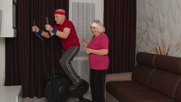 Thumbnail for Active Senior Mature Grandfather Man in Sportswear Using Orbitrek Grandma Encourages Him at Home