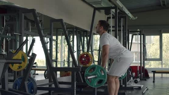 Sportsman Doing Training mit Langhantel und Flexing Muskeln, Training Hände und Rücken im Fitnessstudio