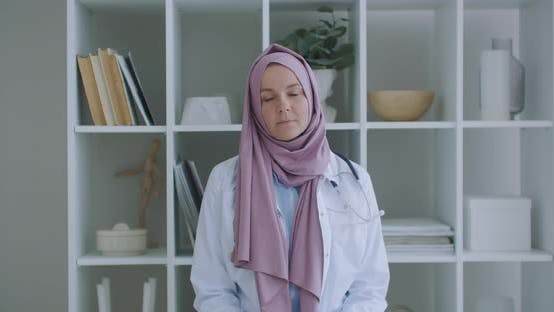 Thumbnail for Looking at the Camera Listening Woman Doctor in Hijab Looks at the Camera and Listens To the Patient