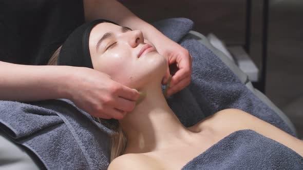 Cosmetologist verwendet spezielle Kosmetikprodukte, um das Gesicht im Spa-Center zu heben