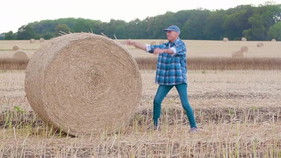 Thumbnail for Smiling Farmer Rolling Hay Bale and Gesturing in Farm