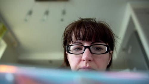 Woman with Glasses at Home Uses Tablet, Bottom View