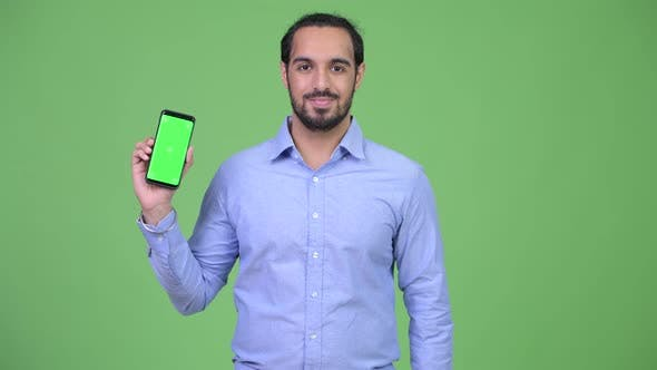 Thumbnail for Young Happy Bearded Indian Businessman Showing Phone and Giving Thumbs Up