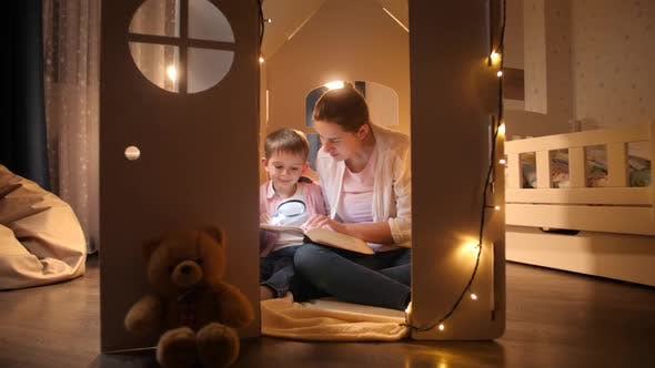 Dolly Shot of Young Mother Reading Book To Her Little Son While Sitting in Small Toy House