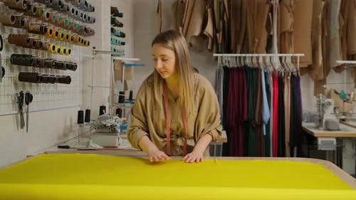 Close up of female designer unwinding a big yellow roll of fabric tissue on table at design studio