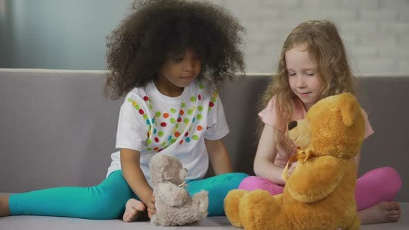 Thumbnail for Two Little Multiracial Girls Sitting on Couch and Playing with Teddy Bears