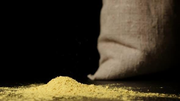 Thumbnail for Turmeric Powder Falling Down On A Table Near A Sac