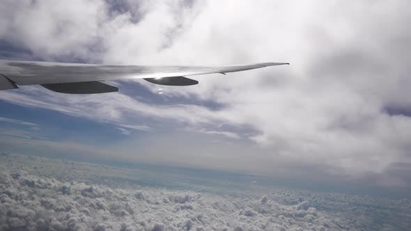 Thumbnail for Aircraft Wing Between Layers of White Clouds High in the Sky at Sunny Weather