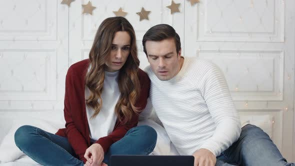 Stressed Couple Watching Horrible News on Computer at Home Together
