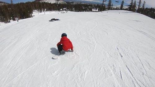 A boy snowboarder snowboarding at a ski resort.