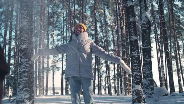 Молодая женщина в зимнем лесу веселая девушка бросает снег и играет с собакой зимой