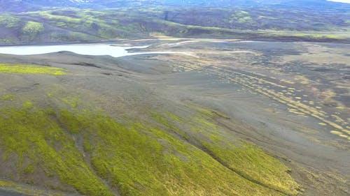 Fliegen über einem Vulkanfeld mit lebendigem grünem Moos in Island