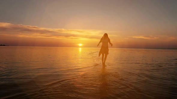 Thumbnail for Brunette Woman in a Dress Running Along Water at Sunset or Sunrise