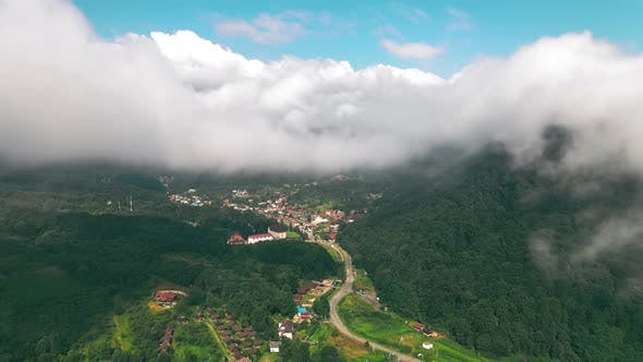 Thumbnail for Aerial View Flight Over the Clouds Through Which You Can See the Village Between the Mountains. View