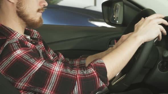 Thumbnail for Cropped Shot of a Bearded Man Sitting in a Car Holding the Steering Wheel
