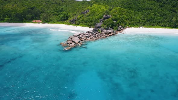 Thumbnail for Aerial Footage Approaching Unique Granite Boulders Surrounded By Crystal Clear Turquoise Blue Ocean