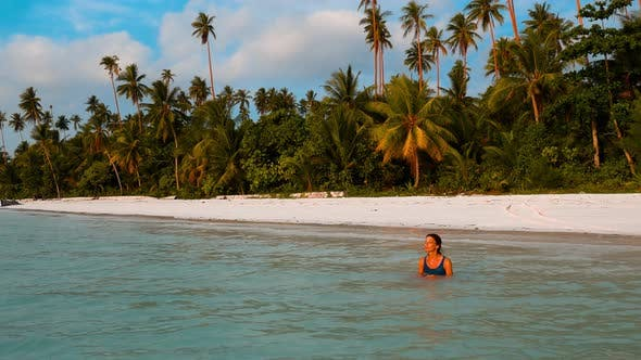Thumbnail for Woman sunbathing in turquoise water white sand beach tropical coastline