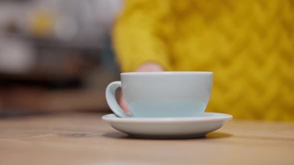 Female Hand Pushing Blue Coffee Cup at Cafeteria Counter