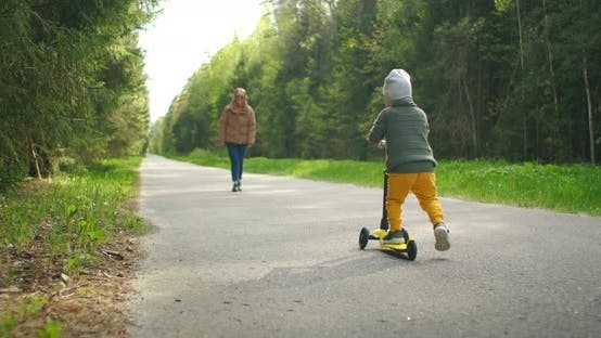 Thumbnail for Mother and Son Drive Scooter Outdoors. He's Always Making Us so Proud. Cute Little Boy Wearing Cap