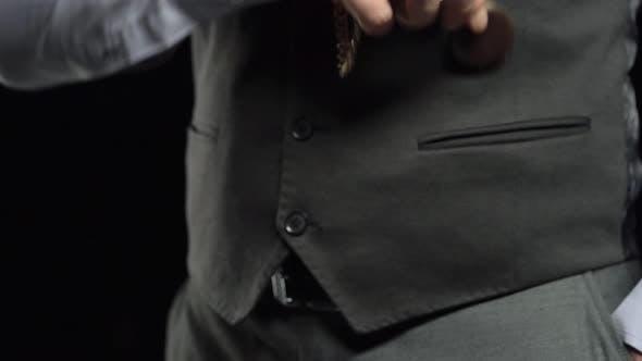 Sammler zieht eine Uhr an einer Kette heraus und legt Zeit in seine Handfläche