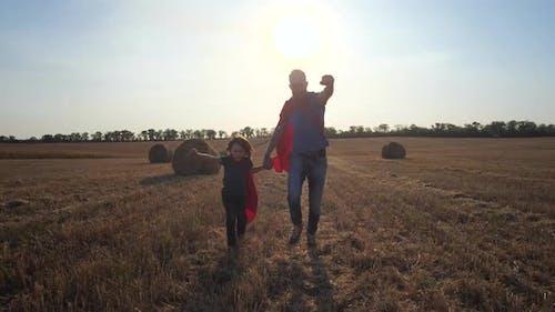 Vater und Sohn als Superhelden laufen über Feld