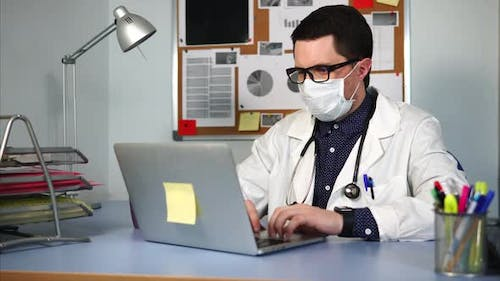 The General Practitioner in Clinic Fills in the Patient's History on the Laptop