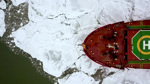 Aerial Epic Red Ship in Winter Sails Through Frozen Sea Makes Its Way. Ice Floe Graphic Pattern