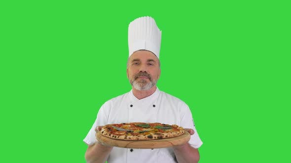 Happy Senior Cook with a Pizza in Hands Looking To Camera on a Green Screen Chroma Key