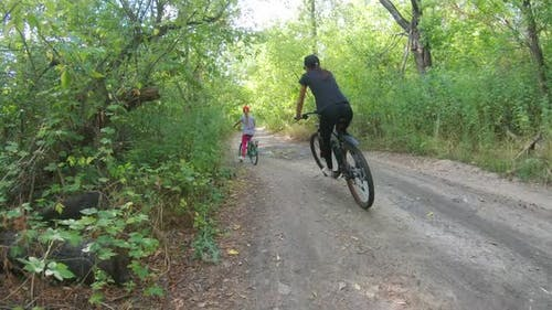 Mom and Daughter Ride Bicycles in the Forest in Summer