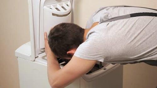Employee Examines Top Loader of Washing Machine Near Wall