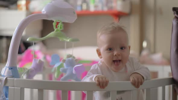 Thumbnail for Cute Baby Girl Playing in a Round Crib