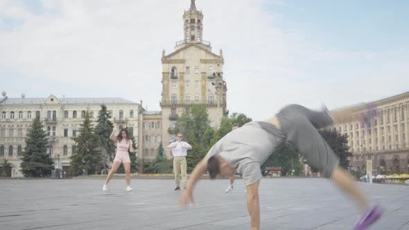 Thumbnail for Brunette Young Man Performing Sportive Dancing Movements on City Square with Friends Dancing at the
