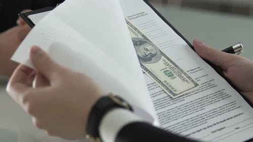 Man Signing Contract With Dollar Bills Inserted, Venality and Financial Crime