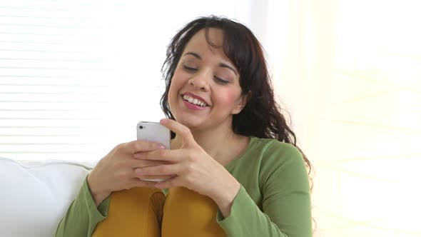 Thumbnail for Young Hispanic woman sitting on couch using smartphone