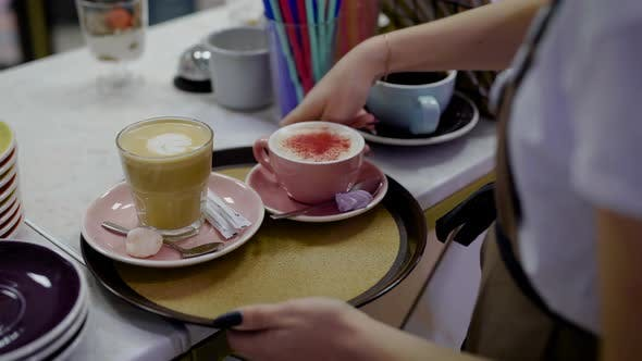 Thumbnail for Female Waiter Is Putting Dessert and Two Mugs with Sweet Coffee on a Round Tray and Carrying It Over