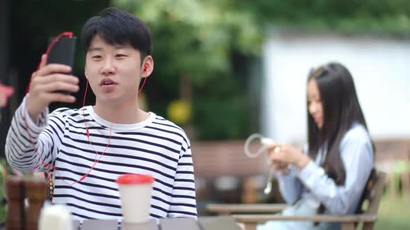 Thumbnail for Asian Boy Video Calling on Smartphone at Cafe Table Outdoors