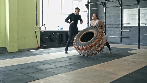 Thumbnail for Woman Performing Tire Flips at Personal Workout with Coach