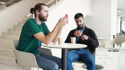 Workers sit on phones at lunch in office cafe